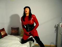 Doll in latex catsuit and female mask have some fun
